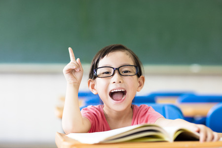kid portrait: happy little girl with idea gesture in the classroom