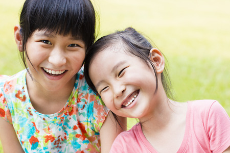 kid smile: closeup Cute little girls on the grass