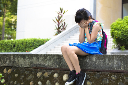 children sad: stress  girl sitting and  thinking in the school Stock Photo