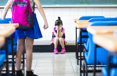 bully: little girl bullying in school classroom Stock Photo