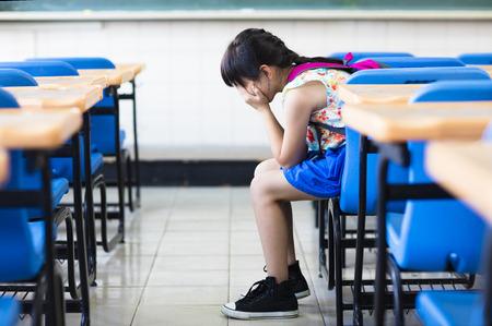 education: 슬픈 소녀 앉아 교실에서 생각 스톡 콘텐츠