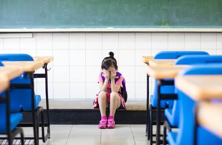 depresion: chica estrés sentado y pensando en el piso del aula