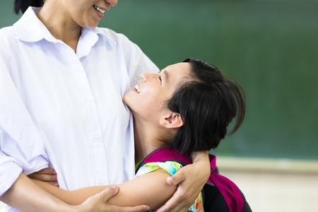 salle de classe: Fille heureux étreignant sa mère dans la classe