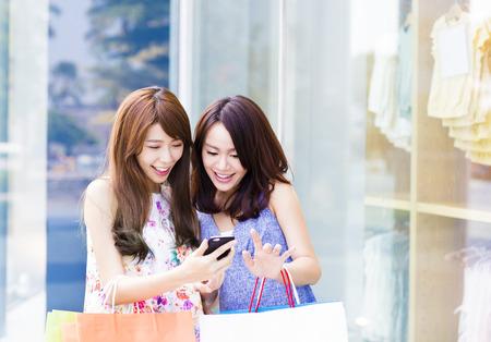 chicas comprando: Mujeres felices con bolsas de compras y ver teléfono Foto de archivo