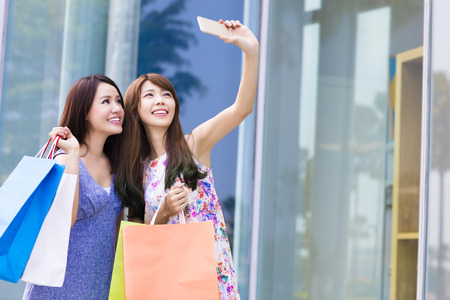 lifestyle shopping: young woman holding shopping bags taking photos with smartphone