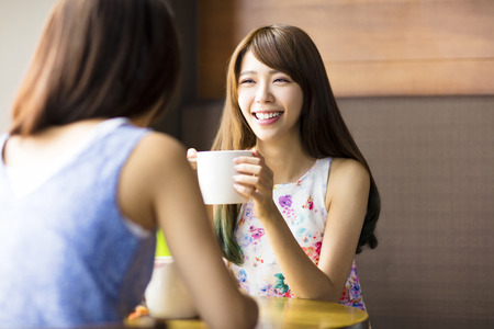 happy young woman: two young woman chatting in a coffee shop