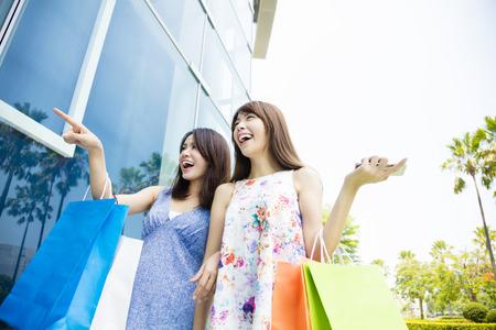 chicas comprando: Feliz mujeres jóvenes con bolsas de la compra