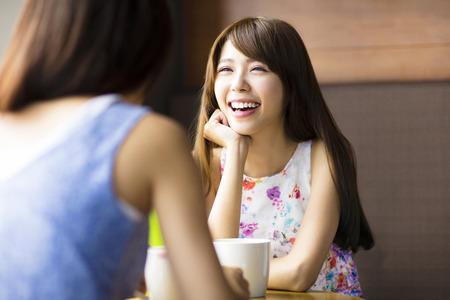 amigos: dos mujeres jóvenes charlando en un café