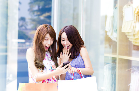 Gelukkige Vrouwen met boodschappentassen en kijken Phone