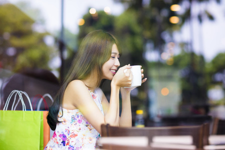 smiling young woman drinking coffee in cafe shop