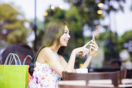 lächelnde junge Frau, die intelligentes Telefon im Café-Shop