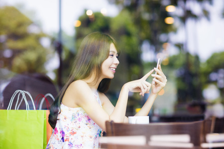 smiling young woman looking at smart phone in cafe shop