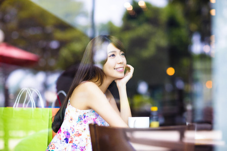 asian lady: smiling young woman thinking in cafe shop
