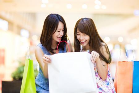 mujeres felices: Mujer feliz que mira la bolsa de compras en el centro comercial Foto de archivo