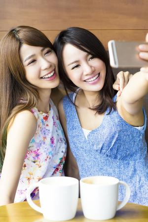 счастливые подруги принимая селфи в кафе Фото со стока