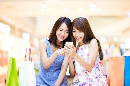 Gelukkige vrouw op zoek naar slimme telefoon bij winkelcomplex Stockfoto