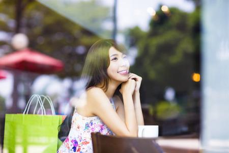 mujer pensando: mujer joven pensando en la tienda de café de la sonrisa