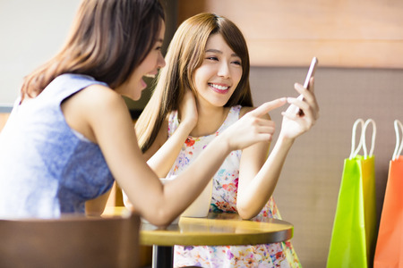 asian ladies: happy young woman looking at phone in coffee shop