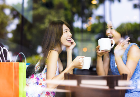 femmes souriantes: deux jeunes femmes discutent dans un caf� Banque d'images