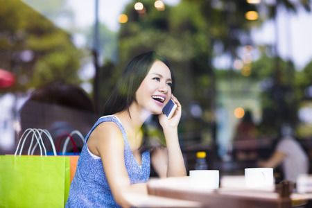 lifestyle shopping: smiling young woman talking on the phone in cafe shop Stock Photo