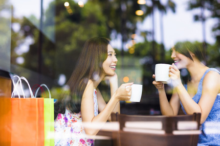 chicas de compras: dos mujeres j�venes charlando en un caf�