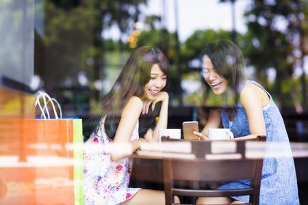 amistad: Mujer joven feliz que mira el teléfono en la tienda de café Foto de archivo