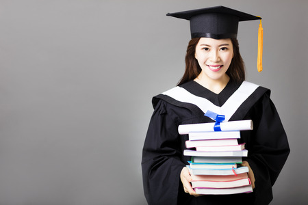 gown: beautiful young  graduate holding diploma and book Stock Photo
