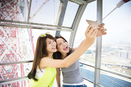happy women girlfriends taking a selfie in ferris wheel Stock Photo