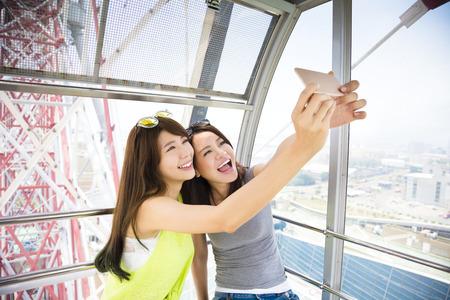 riendo: mujeres felices novias tomar un selfie en noria Foto de archivo