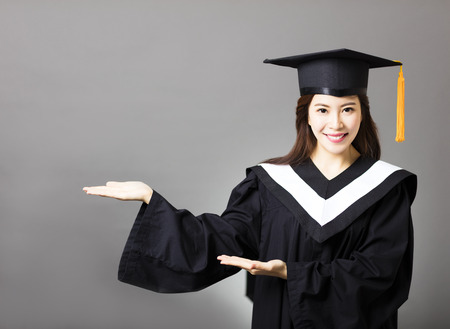 academic robe: beautiful young  graduate with showing gesture