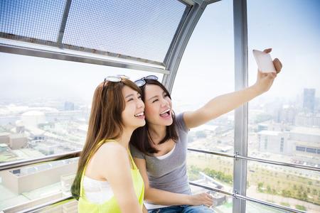 resor: lyckliga kvinnor flickvänner tar en selfie i pariserhjul