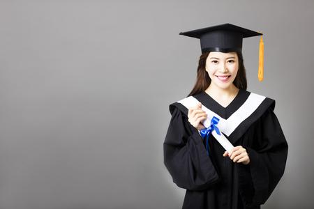 gorros de graduacion: sostiene graduado joven y bella diploma