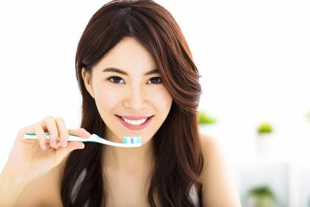 dientes: Mujer joven cepillarse los dientes por la mañana