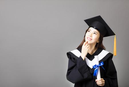 graduado: hermosa joven graduado holding diploma y pensamiento