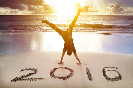 sunny beach: happy new year 2016. young man handstand on the beach Stock Photo