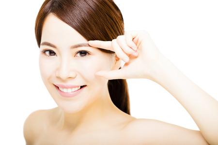 oči: detailním krásná mladá žena, ukázal na oko Reklamní fotografie