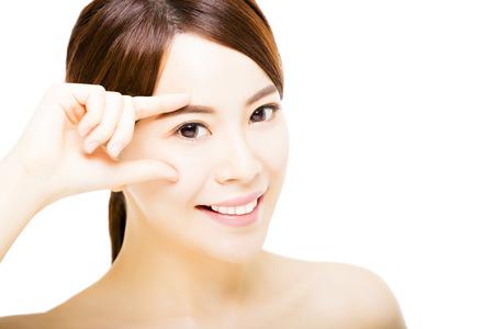 beauté: agrandi belle jeune femme pointant vers l'oeil Banque d'images