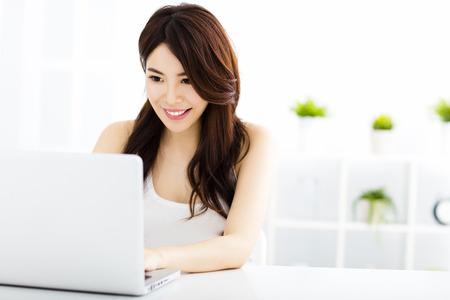 Mujer sonriente joven con ordenador portátil