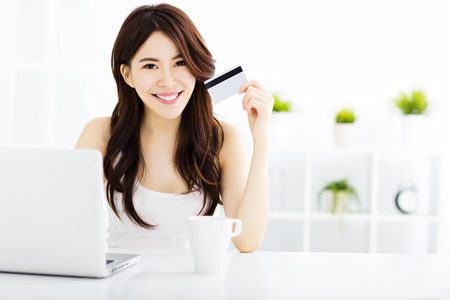mujer alegre: Mujer joven de compras en línea y muestra la tarjeta de crédito