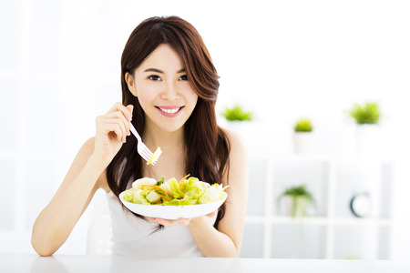 salads: beautiful asian young woman eating healthy food
