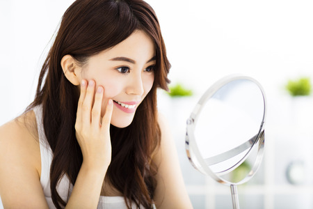 mirror face: Happy young woman  looking on mirror Stock Photo