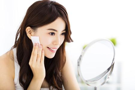 Mooie jonge vrouw die haar gezicht schoonmaakt met katoenen Stockfoto