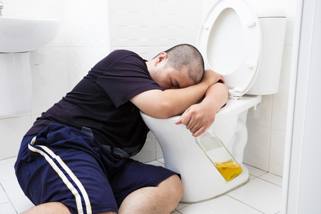 borracho: Hombre gordo borracho con botella de vino en el baño Foto de archivo