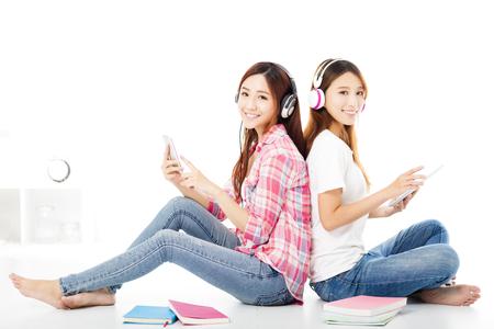 jovenes estudiantes: Feliz de dos estudiantes adolescentes que se sientan en el suelo