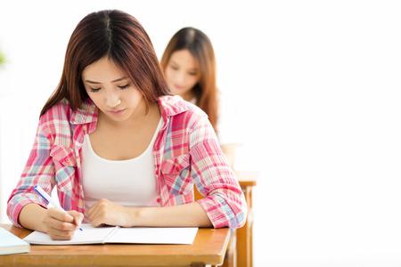 estudiantes: Joven estudiante con otros escribiendo notas en el aula Foto de archivo