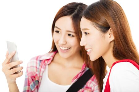 asian group: Two  happy teenage students girls watching the smart phone