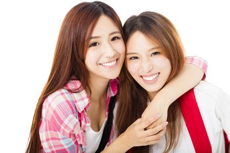 Twee gelukkige tiener studenten meisjes op wit wordt geïsoleerd Stockfoto