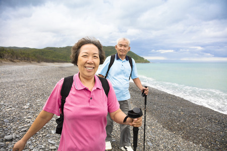 old lady: happy senior couple hiking on the coast beach