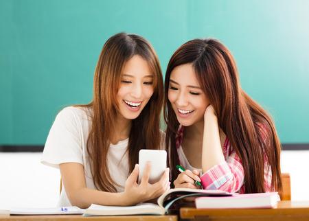 gente exitosa: estudiantes felices niñas que miran el teléfono inteligente en el aula