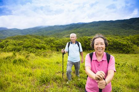 active holiday: happy senior couple hiking on the mountain Stock Photo
